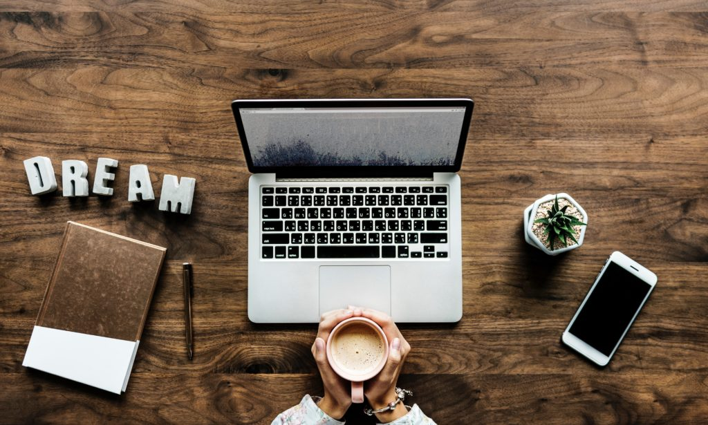 Person sat at laptop with coffee cup