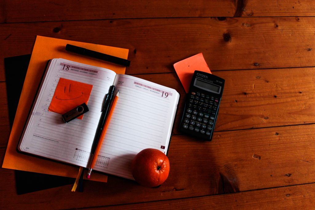 Diary with a pen, an orange and a calculator on floorboards