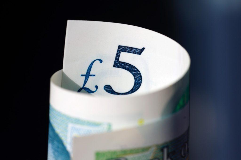 Rolled up British five pound note