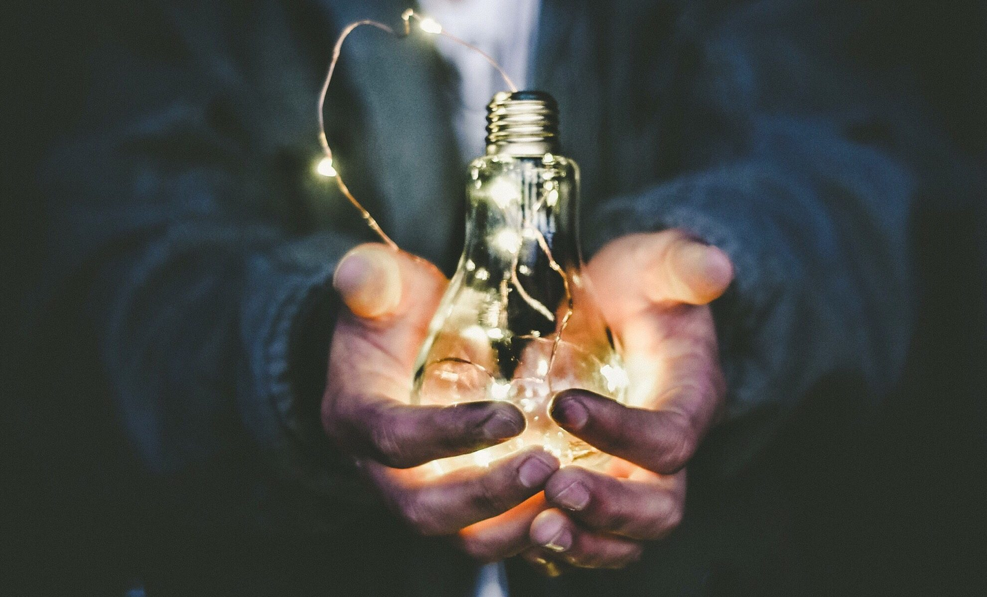 man holding lightbulb in hands